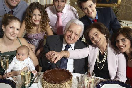 40 something: Grandparents with multigenerational family cutting cake