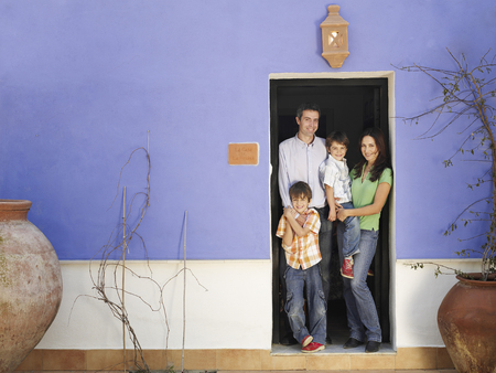 fulfilled: Parents and twin sons (4-6) standing in doorway, smiling, portrait