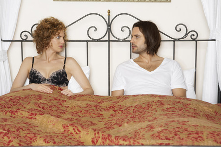 young couple sitting in bed wearing underwear looking at each other LANG_EVOIMAGES