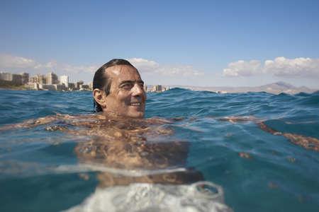 50 something: Mature man swimming in sea, smiling