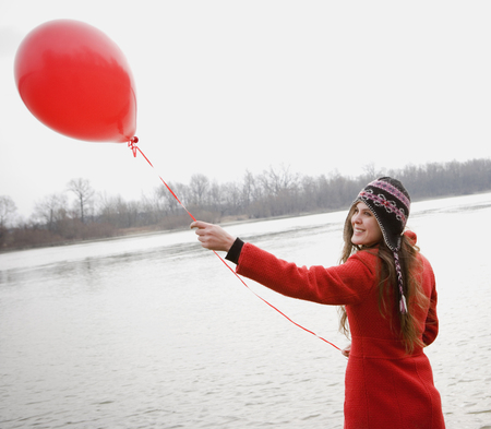 turn of the year: Young woman standing by river holding red balloon, smiling LANG_EVOIMAGES