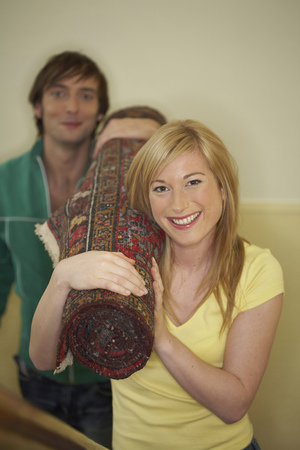 appearance: Young couple carrying rolled up rug smiling, portrait