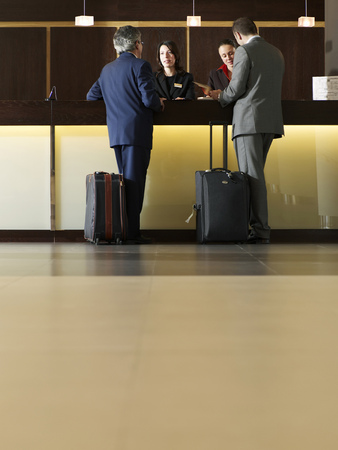 Two businessmen standing at hotel reception LANG_EVOIMAGES