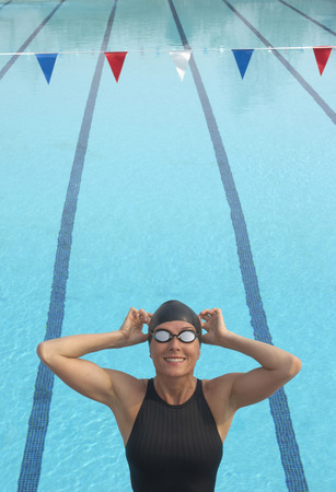 formulate: Female swimmer adjusting goggles by pool, smiling