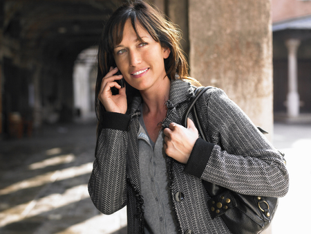 Woman talking on mobile phone. Venice, Italy. LANG_EVOIMAGES