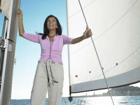 passtime: Mature woman standing on yacht, smiling
