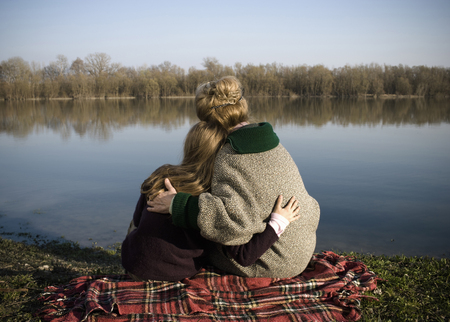 Grandmother and granddaughter (10-12) sitting by river, rear view