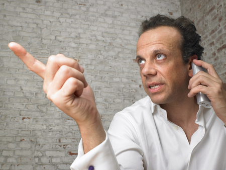 appearance: Businessman talking on the telephone, pointing finger. ,Brussels, Belgium.