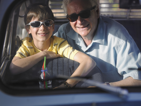 family unit: Boy (8-10) and grandfather in sunglasses sitting in backseat of car, portrait LANG_EVOIMAGES