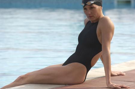 Female swimmer wearing swimming cap sitting on edge of pool