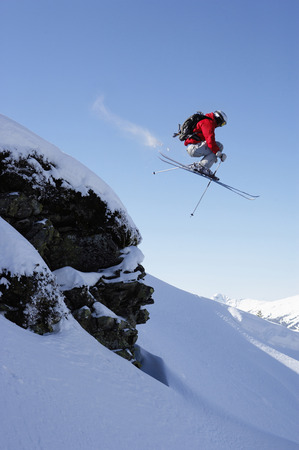 Austria, Saalbach, male skier jumping over rock on snow covered slope LANG_EVOIMAGES