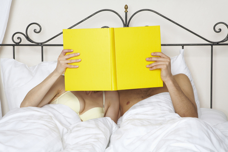 young couple in bed holding yellow book up together LANG_EVOIMAGES