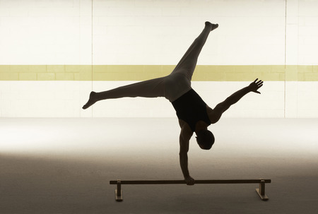 Male gymnast balancing on one hand on floor bar, rear view