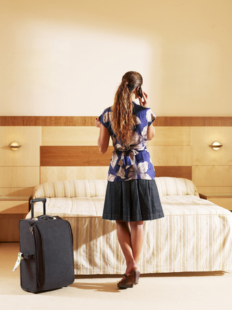Woman standing in hotel bedroom using cell phone, rear view