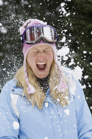 Snowball exploding on young blonde woman wearing ski-wear in forest