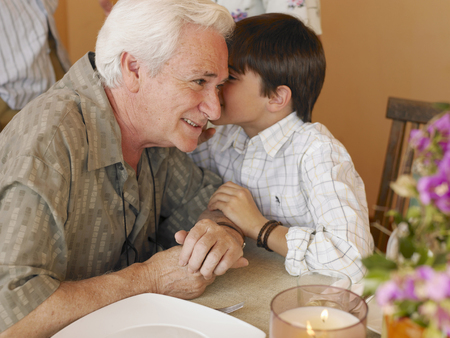 rumour: Boy (8-10) whispering in grandfathers ear at dining table