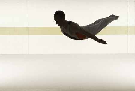 Male gymnast performing somersault in floor exercise
