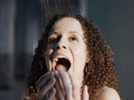 Woman beneath shower, smiling