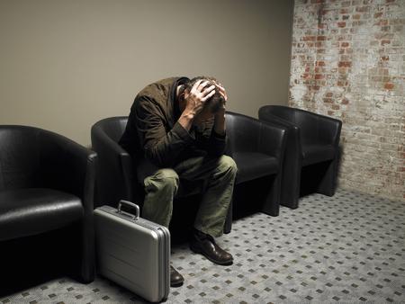 Anxious businessman in waiting room, head in hands. Brussels, Belgium.