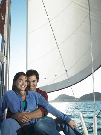 passtime: Young couple relaxing on yacht, smiling, portrait