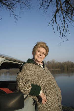 passtime: Senior woman leaning on car by riverside, smiling, portrait LANG_EVOIMAGES