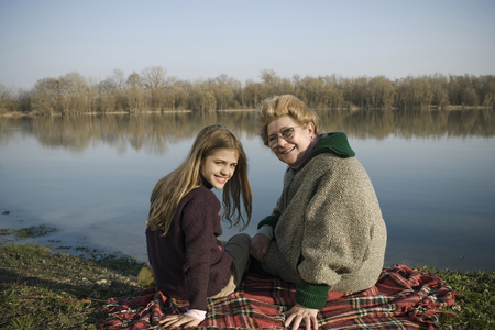Grandmother and granddaughter (10-12) sitting on rug by river, smiling