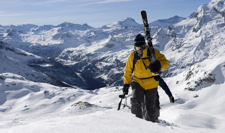 Two male skiers walking up mountain ridge carrying skis LANG_EVOIMAGES