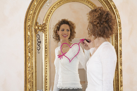 woman drawing heart on mirror with lipstick
