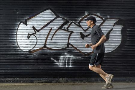 Male runner passing graffiti in street, side view