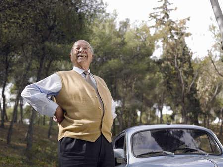 passtime: Senior man standing beside parked car, hand on hip, smiling, portrait LANG_EVOIMAGES