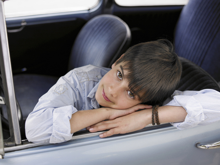 passtime: Boy (8-10) sitting in car, leaning out of open window, portrait