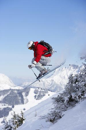 Austria, Saalbach, male skier jumping past trees on slope