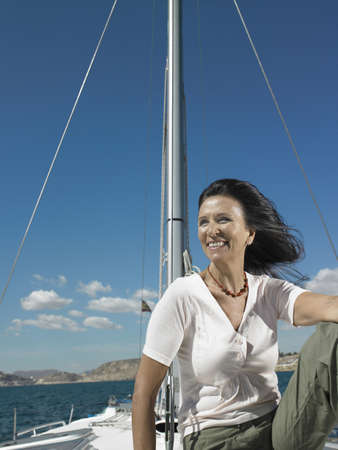 50 something: Mature woman relaxing on yacht, smiling