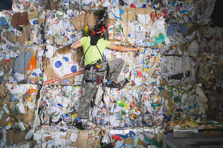 mitre: Man climbing a wall of recycling.