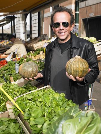 Man choosing vegetables at Rialto market. Venice, Italy.