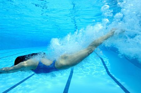 Woman diving in swimming pool, underwater view