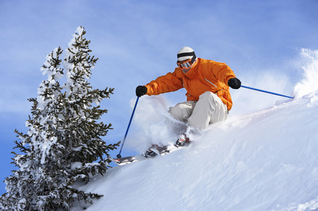 Austria, Saalbach, man skiing over ridge on slope LANG_EVOIMAGES