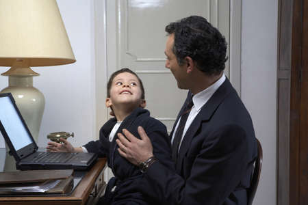 40 something: Son (4-6) smiling at father while using laptop