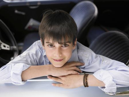 appearance: Boy (8-10) sitting in car, leaning out of open window, portrait