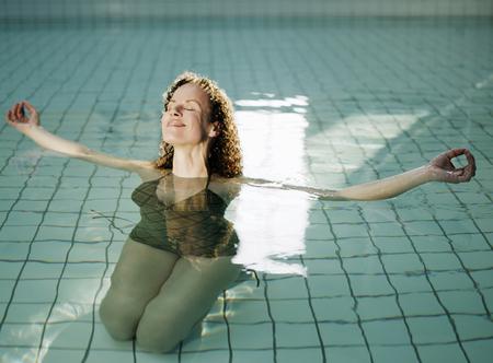 Woman meditating in swimming pool, smiling