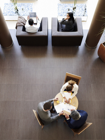 Two businessmen and woman having meeting, overhead view