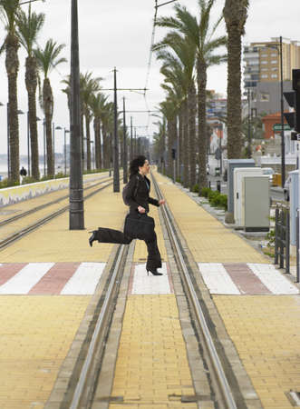 promptly: Businesswoman running across pedestrian crossing on tramway