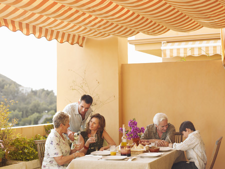 Multi-generational family talking at dining table on balcony, man pouring wine LANG_EVOIMAGES