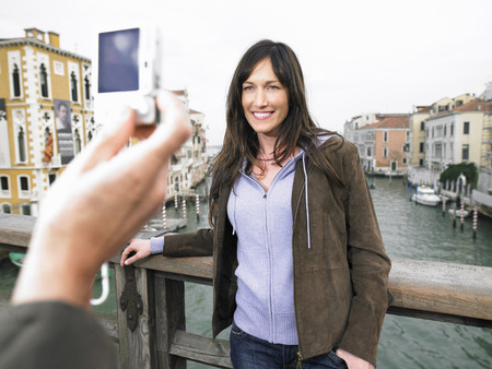thirtysomething: Close up of mans hand taking photograph of woman. Grand Canal, Venice, Italy. LANG_EVOIMAGES