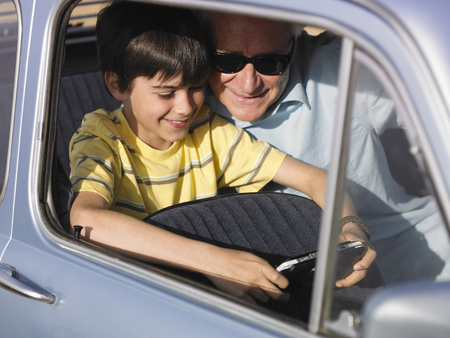 50 something: Boy (8-10) and grandfather playing portable video game in backseat of car LANG_EVOIMAGES