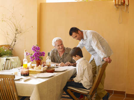 grand sons: Boy (8-10) with father and grandfather at dining table on balcony LANG_EVOIMAGES