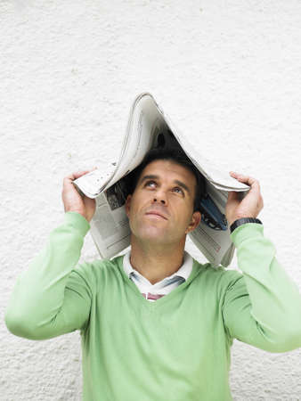 40 something: Man covering head with newspaper, looking up