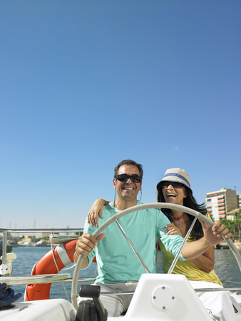successfulness: Mature couple wearing sunglasses at wheel of yacht, smiling LANG_EVOIMAGES