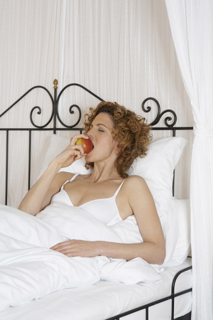 woman in bed biting apple