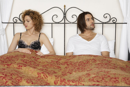 young couple sitting in bed wearing underwear looking away from each other LANG_EVOIMAGES